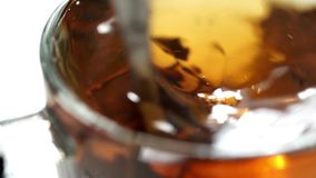 Spoon stirs the brew tea in a transparent cup. Pouring tea into the cup and stir sugar stock footage