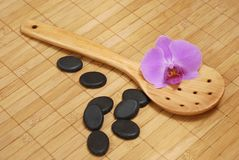 Spoon with stones and the orchid Stock Photos