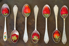 Spoon with strawberries on  metal surface. Water drops. top vie Stock Images