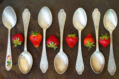 Spoon with strawberries on metal surface. Water drops Stock Photo