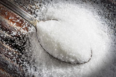 Spoon of sugar. An over flowing spoon of sugar on wooden background Stock Image