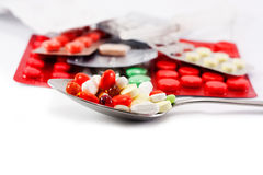 Spoon with tablets. Spoonful of pills and in the background package of tablets Stock Images