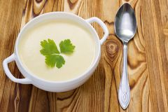 A spoon and tasty potato soup with a leaf of parsley, rustic wooden table. Potato and onion vegan, vegetarian healthy cream soup i. N white ceramic bowl royalty free stock image