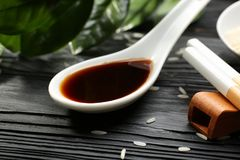 Spoon with tasty soy sauce on wooden table, stock photography