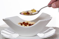 Spoon of vitamins over bowl of tablets Stock Photo