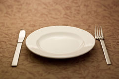 Spoon and white plate. Knives and forks and dishes were placed on the table Royalty Free Stock Images