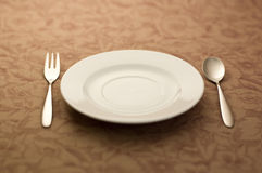 Spoon and white plate. Spoon and fork and plate was placed on the table Stock Photo