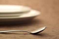 Spoon and white plate. Spoon on the table and tableware Stock Image