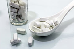 Spoon white with some pills. Concept of health Royalty Free Stock Photography
