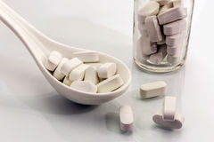 Spoon white with some pills. Concept of health Royalty Free Stock Photos