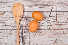 Spoon, wire whisk and two brown eggs Royalty Free Stock Photos