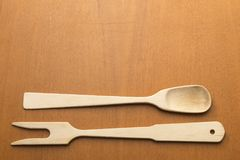 Wooden spoon and fork on brown background. A spoon and a wooden fork placed in the opposite direction on a brown background Royalty Free Stock Photo