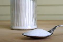 Spoonful ammucchiante di zucchero Fotografie Stock
