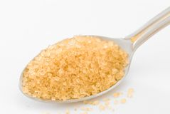 Spoonful Of Brown Sugar. A spoonful of brown sugar on a white background Royalty Free Stock Photo