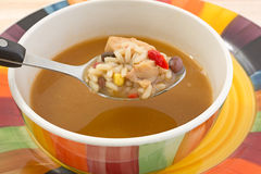 Spoonful of chicken soup with bowl Stock Photos