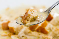 Spoonful of Creamy Soup with Crouton. Extreme Close Up of Spoonful of Hearty Creamy Soup with Toast Bread Crouton in front of Bowl of Soup Picture Out of Focus stock photos