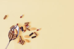 A spoonful of drugs. A spoonful of pills, tablets and medicaments on yellow background Stock Photography
