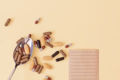 A spoonful of drugs. A spoonful of pills and tablets on yellow background with a prescription Stock Photo