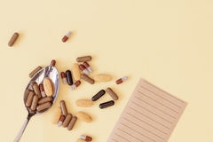 A spoonful of drugs. A spoonful of pills and tablets on yellow background with a prescription Royalty Free Stock Photo