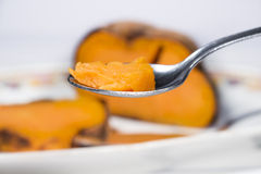 Spoonful in front of ceramic tray with roasted sweet potato Stock Photo