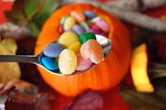 Spoonful of Halloween Candy. A close up of a carved out pumpkin filled with candy and candy on a spoon royalty free stock image