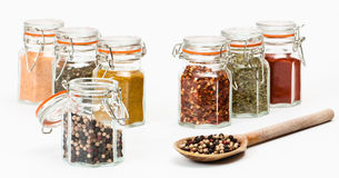 Spoonful Of Peppercorns. Rustic spoon full of peppercorns with spice jars on white background royalty free stock photo