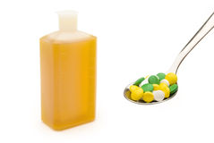 Spoonful of pills and medicine bottle Stock Photos
