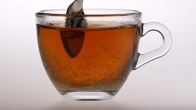 Spoonful sugar stirred a small cup of tea. Slow motion. Spoonful sugar stirred a small cup of tea, spoon first pour the sugar and then stir, sugar is dissolved stock footage
