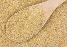 Spoonful of turbinado sugar. Close view of a spoonful of turbinado sugar atop more sugar Royalty Free Stock Photos