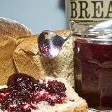 Spooning jam onto hot fresh bread. Slice of freshly made grainy bread, with country style plate and board, hand spooning on home made preserve, butter and jam Royalty Free Stock Image