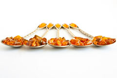 Spoons with amber 4. Five silver spoons with amber on a white background Royalty Free Stock Images