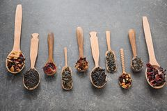 Spoons with different types of dry tea leaves on grey background royalty free stock photo