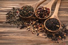 Spoons with different types of dry tea leaves on wooden background stock photo