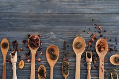 Spoons with different types of dry tea leaves on wooden background stock photos