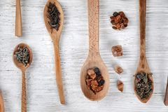 Spoons with different types of dry tea leaves on wooden background stock photography