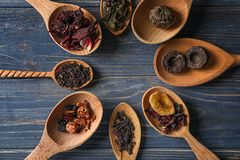 Spoons with different types of dry tea leaves on wooden background royalty free stock images