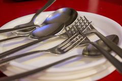 Spoons and folks in white plates in a restaurant. royalty free stock photo