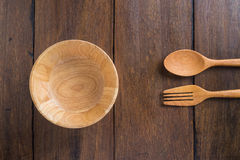 Spoons, forks, wooden bowl on wooden background Stock Photos