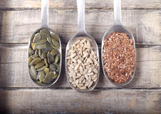 Spoons full of seeds. On wooden background Stock Images