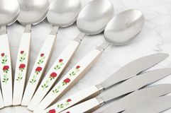 Spoons and knives on white gray background royalty free stock photo