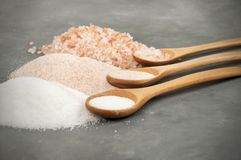 Spoons with pink salt. Three colors of Himalayan salt with spoons on grey, concrete background stock photos