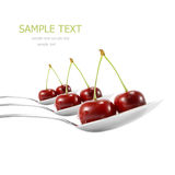 Spoons with ripe cherry. Isolated on white Stock Photos