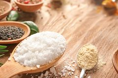 Spoons with salt and different spices on wooden table, closeup stock images