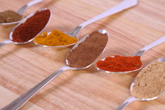 Spoons Of Spice. Six different ground spice powders in silver spoons on a wooden background Royalty Free Stock Photography