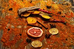 Spoons with spices on wooden texture. Spices scattered all over wooden surface. Spoons filled with cinnamon, grinded red. Pepper and curcuma powder and kitchen royalty free stock photos