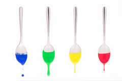 Spoons suspended bathed in colored paint with the paint runny Royalty Free Stock Photography