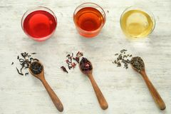 Spoons with variety of dry tea leaves and cups of aromatic drinks on wooden background royalty free stock image