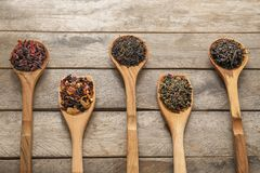 Spoons with variety of dry tea leaves on wooden background royalty free stock images
