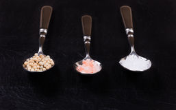 Spoons with a variety of spices on natural black slate stone. Close up three old spoons contains various spices on natural black slate stone. Selective focus on stock photo