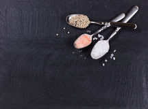 Spoons with a variety of spices on slate background. Overhead view of three old spoons containing various spices in upper left hand corner of natural black slate royalty free stock photos